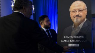 """Justice For Jamal"" Campaign leader Ahmed Bedier (C) adjust the portrait of late Washington Post journalist Jamal Khashoggi during a remembrance ceremony for him in Washington, DC, on November 2, 2018. (Photo by Jim WATSON / AFP)"