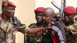 """(FILES) In this file photo taken on October 29, 2018 members of the armed forces arrest Central African MP Alfred Yekatom aka """"Rambo"""" (C), who represents the southern M'baiki district former militia leader, after he fired the gun at the parliament in Bangui. - Central African MP Alfred Yekatom aka """"Rambo"""" was extradited on November 17, 2018 to The Hague, The Netherlands, after an arrest warrant was issued by the International Criminal Court. (Photo by Gael GRILHOT / AFP)"""