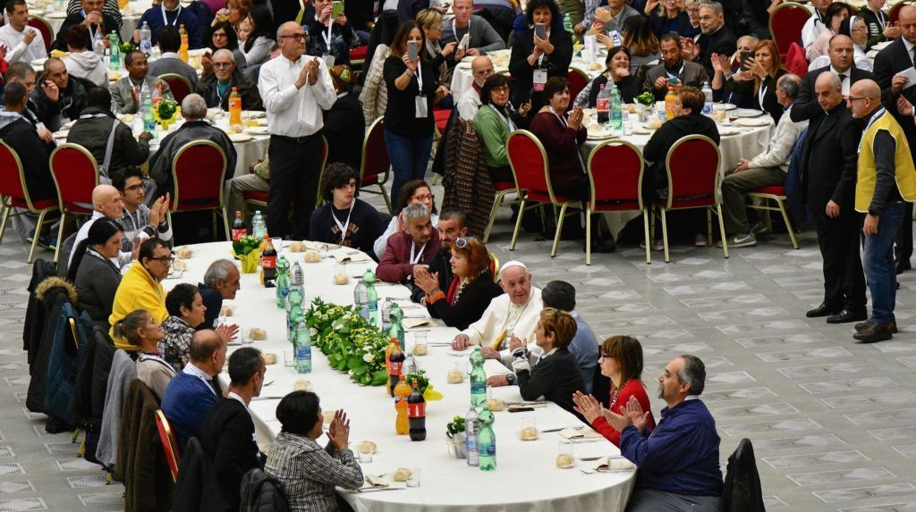 "Pope Francis (C-Bottom) has a lunch with destitute people, on November 18, 2018, at the Paul VI audience hall in Vatican, to mark the World Day of the Poor. - Pope Francis railed against social inequality on November 18, 2018, lamenting ""the din of the rich few"" drowning out the voice of the needy, as he marked the second ""World Day of the Poor"". (Photo by Vincenzo PINTO / AFP)"