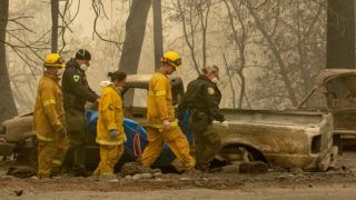 (FILES) In this file photo taken on November 14, 2018 Rescue workers carry a body away from a burned property in the Holly Hills area of Paradise, California/ - The fire that has ravaged northern California is now almost completely contained, authorities said on November 22, 2018, as the death toll rose to 84. The number of people listed as unaccounted for in the deadliest and most destructive fire in state history stands at 563. (Photo by Josh Edelson / AFP) / ALTERNATIVE CROP