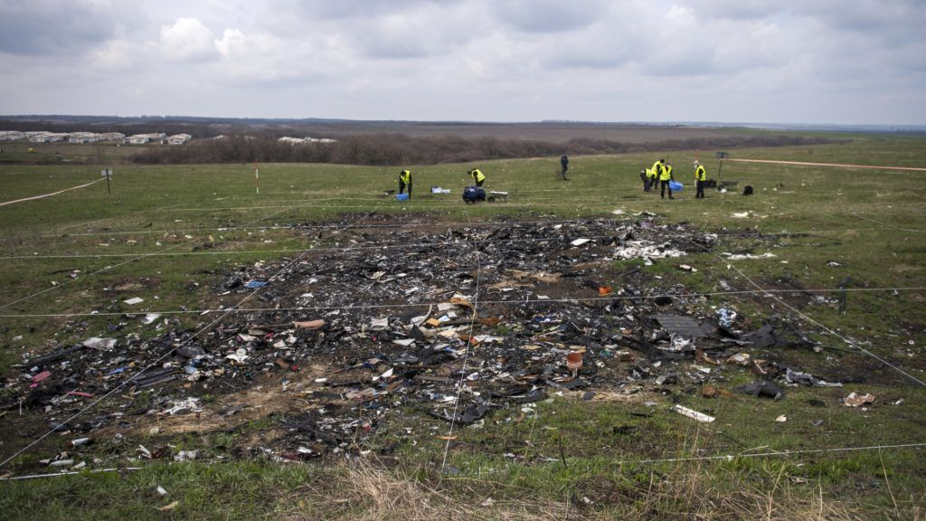 Dutch and Malaysian investigators and local authorities work, on April 16, 2015 at the MH17 plane crash site near the village of Grabove in the self-proclaimed Donetsk People's Republic (DNR) as Dutch and international investigators are renewing their search for body parts and debris in restive eastern Ukraine, including at a location previously considered unsafe, the team's chief announced on the eve. All 298 passengers and crew onboard the Malaysia Airlines jetliner -- the majority of them Dutch -- died when it was shot down over war-torn eastern Ukraine last year.  AFP PHOTO / ODD ANDERSEN (Photo by ODD ANDERSEN / AFP)