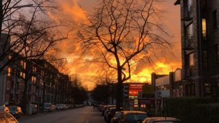 dpatop - 27 November 2018, Hamburg: In the Winterhude district, the light breaking in the clouds at a sunset creates the impression of a large fire. Photo: Axel Heimken/dpa