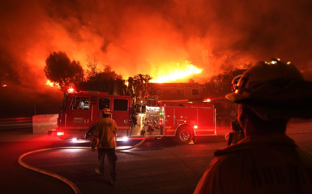 LOS ANGELES, CA - NOVEMBER 09: Los Angeles County firefighters look on as the out of control Woolsey Fire explodes behind a house in the West Hills neighborhood on November 9, 2018 in Los Angeles, California. About 75,000 homes have been evacuated in Los Angeles and Ventura counties due to two fires in the region.   Kevork Djansezian/Getty Images/AFP
