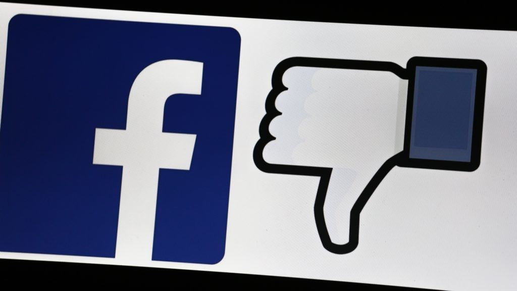 The logo of Facebook and a thumb down is seen on a screen. (Photo by Alexander Pohl/NurPhoto)