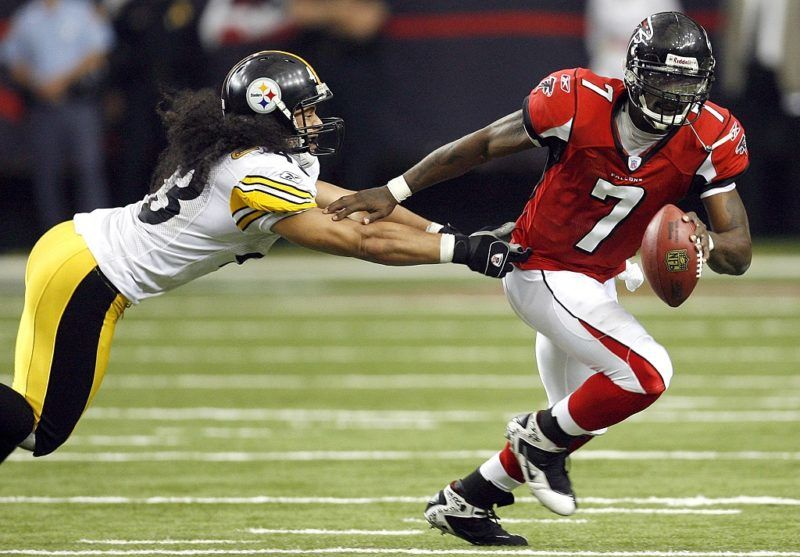 Atlanta quarterback Michael Vick (7) breaks away as he stiff arms Pittsburgh safety Troy Polamalu (left) in overtime of the Falcons 41-38 win Sunday, October 22, 2006, at the Georgia Dome in Atlanta, Georgia. (Photo by Kevin C.  Cox/Getty Images)