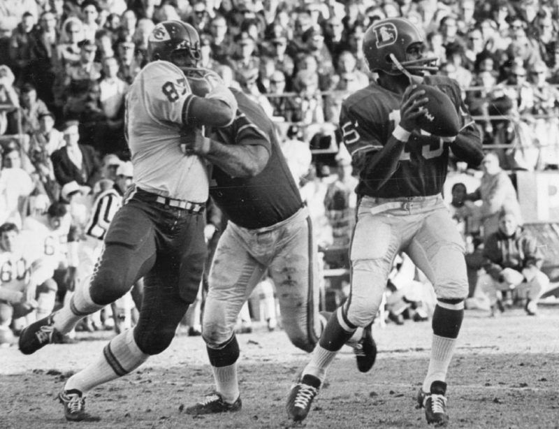 DEC 14 1968, DEC 15 1968 Denver Broncos (Action) Denver quarterback Marlin Briscoe is unaware that a battle is occurring behind him in the first quarter Saturday. Denver's Sam Brunelli is shown holding Kansas City's Aaron Brown while Briscoe prepares to let loose with a pass. Credit: Denver Post (Denver Post via Getty Images)