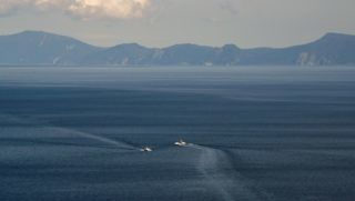 This picture taken on October 10, 2018 shows Kunashiri island, part of an archipelago under Russian control, visible from the Rausu Kunashiri Observatory Deck in Rausu, Hokkaido prefecture. - Four of the islands known as the Northern Territories in Japan and the southern Kuril islands in Russia are disputed and remain a bitter sticking point between Tokyo and Moscow, preventing them from signing a formal peace treaty. Now, former residents who were children when the Soviet troops arrived are heading into their twilight years with little expectation of returning to their former home. (Photo by Kazuhiro NOGI / AFP) / TO GO WITH AFP STORY JAPAN-RUSSIA-DIPLOMACY-POLITICS-WWII,FEATURE BY MIWA SUZUKI