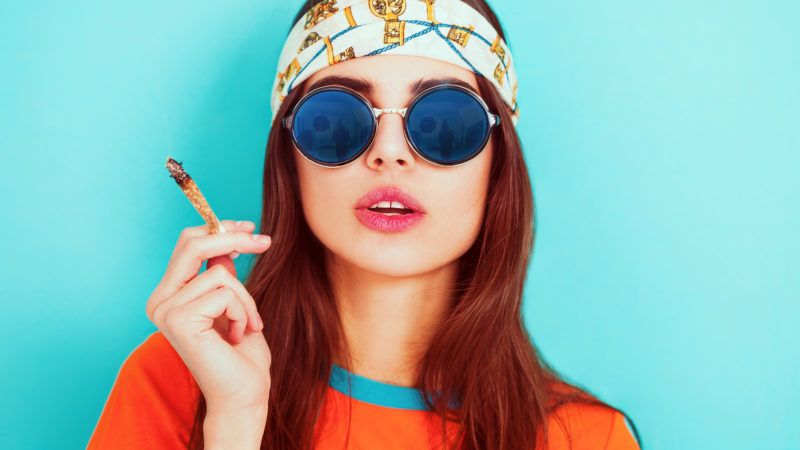 Hippy girl smoking weed and wearing sunglasses