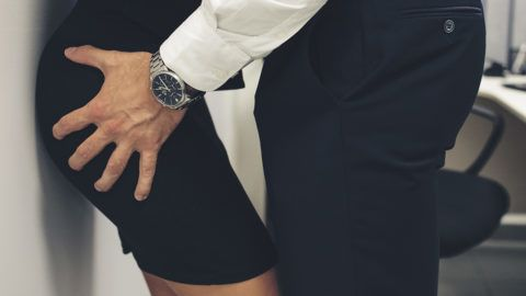 Man touching woman's butt, sexual harassment in office