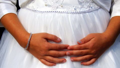 Cute little cild bridesmaid in white dress with hands on her belly