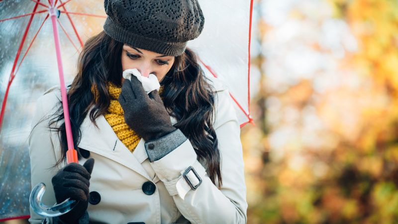Sad woman with cold or flu blowing her nose with a tissue under autumn rain. Brunette female sneezing and wearing warm clothes against cold weather. Illness, depression and allergy concept.