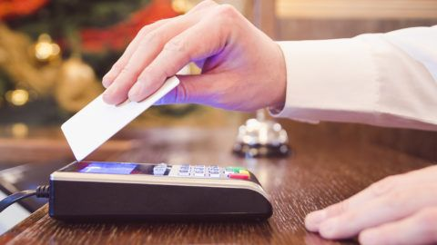 Caucasian male in white shirt paying bill with contactless credit card.