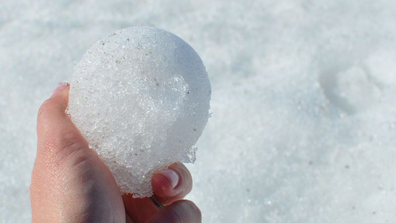 The perfect snow ball being held by a hand