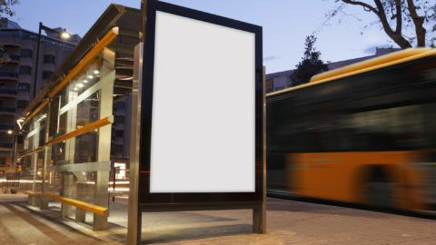 Blank advertisement in a bus stop, with blurred bus