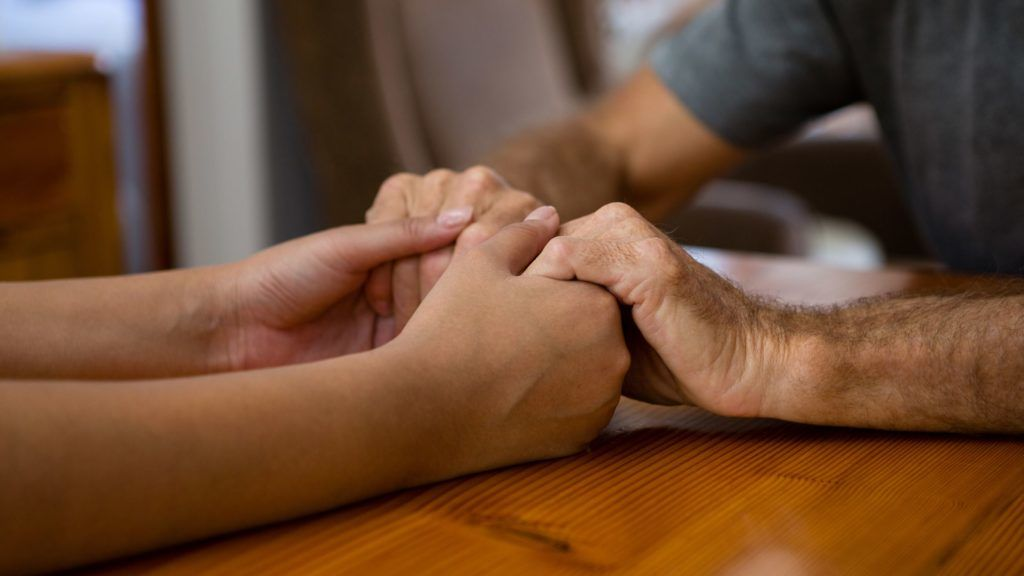 Cropped image of female doctor and senior man holding hands at table