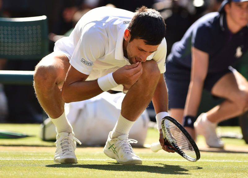 Serbia's Novak Djokovic eats some grass from the court as he celebrates after beating South Africa's Kevin Anderson 6-2, 6-2, 7-6 in their men's singles final match on the thirteenth day of the 2018 Wimbledon Championships at The All England Lawn Tennis Club in Wimbledon, southwest London, on July 15, 2018. (Photo by Glyn KIRK / AFP) / RESTRICTED TO EDITORIAL USE