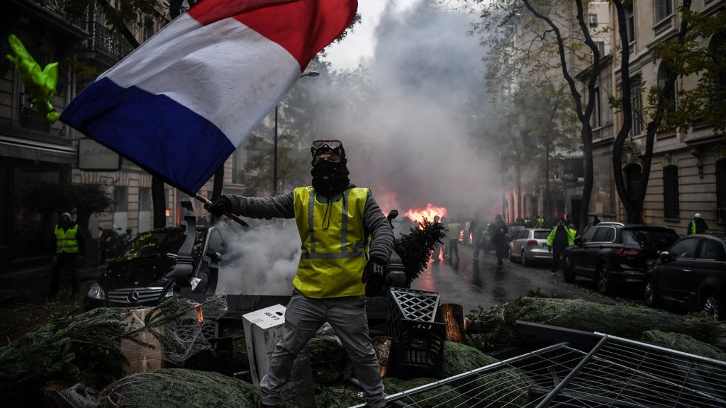 A demonstrator holds a French flag during a protest of Yellow vests (Gilets jaunes) against rising oil prices and living costs, on December 1, 2018 in Paris. - Speaking at the Paris police's command centre, French Prime Minister said 36,000 people were protesting across France, including 5,500 in the capital for this 3rd nationwide day of blockade ands demos. (Photo by Alain JOCARD / AFP)