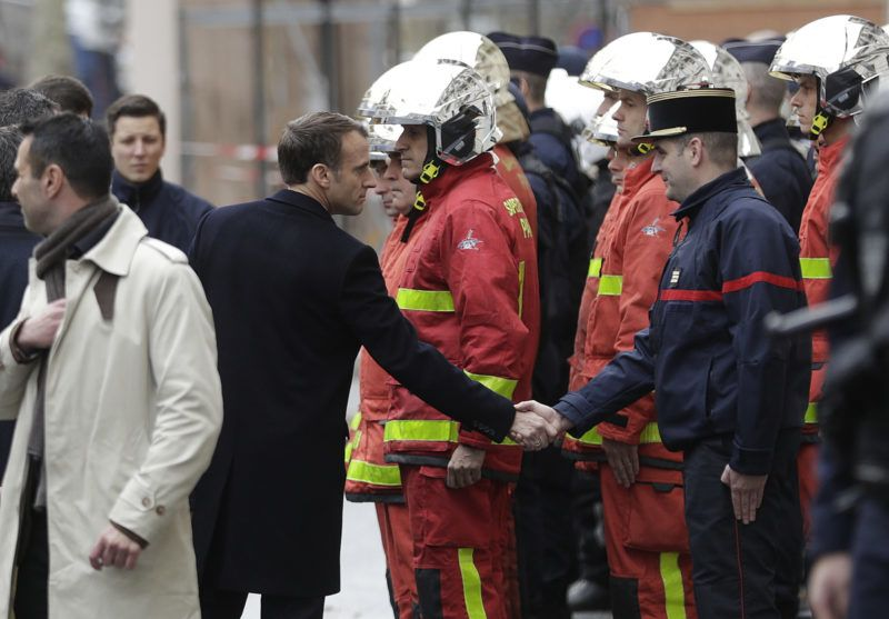 """French President Emmanuel Macron (L) shakes hands with a firefighter during a visit in the streets of Paris on December 2, 2018, a day after clashes during a protest of Yellow vests (Gilets jaunes) against rising oil prices and living costs. - Anti-government protesters torched dozens of cars and set fire to storefronts during daylong clashes with riot police across central Paris on December 1, as thousands took part in fresh """"yellow vest"""" protests against high fuel taxes. (Photo by Geoffroy VAN DER HASSELT / AFP)"""