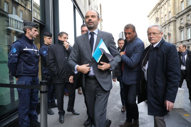 French Prime Minister Edouard Philippe (C) arrives to announce the suspension on rising fuel taxes in Paris on December 4, 2018, a few days after the protests by the 'yellow vest' (gilets jaunes) movement. - The French government plans to announce on December 4 the suspension of fuel tax increases slated for January in a bid to quell the fierce protests which have ballooned into the deepest crisis of Emmanuel Macron's presidency, sources said. (Photo by ludovic MARIN / AFP)