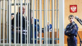 Serial killer Mikhail Popkov stands inside a defendants' cage during a court hearing in Irkutsk on December 10, 2018. - A Siberian policeman who raped and killed women after offering them late-night rides was found guilty of dozens more murders on December 10, 2018, making him Russia's most prolific serial killer of recent times. A court in the city of Irkutsk found Mikhail Popkov guilty of 56 murders between 1992 and 2007, sentencing him to a second life term. He was already in prison after being convicted of killing 22 women in 2015. (Photo by Anton KLIMOV / AFP)
