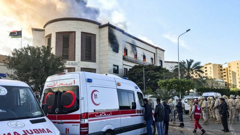A picture taken on December 25, 2018 shows ambulances, paramedics, and security officers at the scene of an attack outside the Libyan foreign ministry headquarters in the capital Tripoli. - At least one person was killed on December 25 as attackers stormed Libya's foreign ministry after a car bomb exploded in front of the building and a suicide bomber then struck inside, a security source at the scene told AFP. (Photo by Mahmud TURKIA / AFP)