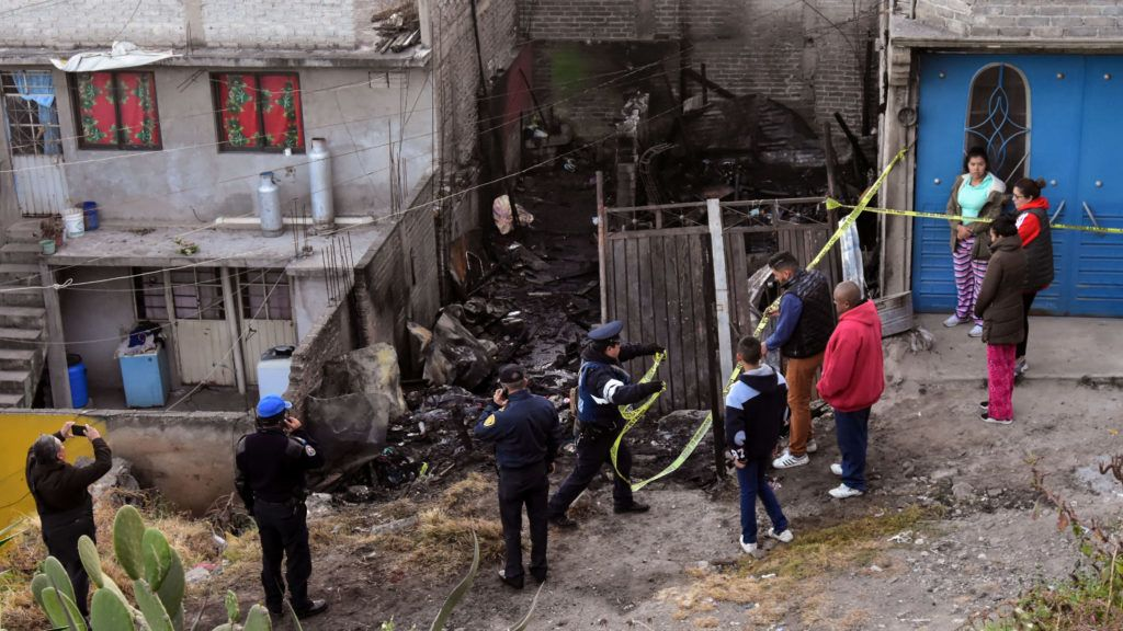 Firefighters and police officers work at the scene of a fire in which seven children died in Iztalapala east of Mexico City on December 28, 2018. - Seven children died Friday during a fire in a shack located in the populated area of Iztapalapa, in the east of the Mexican capital, authorities said. (Photo by DANI ALPIDE / AFP)