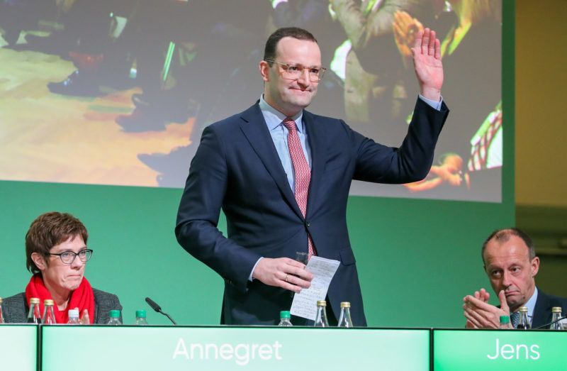 01 December 2018, Saxony, Leipzig: One of the three candidates for the CDU presidency, Jens Spahn (M), waves after his speech at the state party conference of the CDU-Saxons. The two other candidates, Annegret Kramp-Karrenbauer and Friedrich Merz, react to his speech. The presentation of the candidates is the last one before the election to the party chairmanship. A federal party conference on December 7 will decide on the succession of Chancellor Merkel to the party leadership. Photo: Jan Woitas/dpa-Zentralbild/dpa