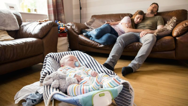 Husband and wife having a nap on the sofa while their newborn baby boy sleeps in a baby bouncer.