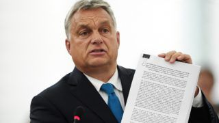 Hungary's Prime Minister Viktor Orban shows a document during a debate concerning Hungary's situation as part of a plenary session at the European Parliament in Strasbourg, eastern France on September 11, 2018. (Photo by FREDERICK FLORIN / AFP)