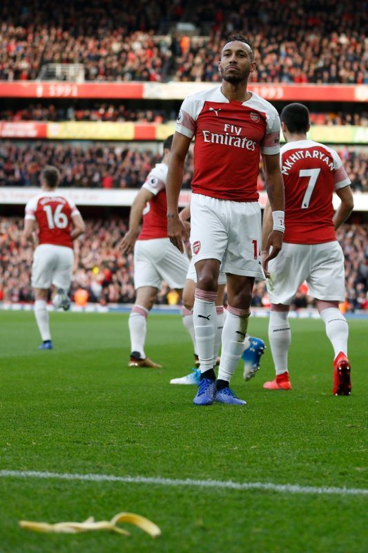 A banana thrown from the crowd is seen at the side of the pitch as Arsenal's Gabonese striker Pierre-Emerick Aubameyang (C) celebrates after scoring the opening goal from the penalty spot during the English Premier League football match between Arsenal and Tottenham Hotspur at the Emirates Stadium in London on December 2, 2018. (Photo by Ian KINGTON / IKIMAGES / AFP) / RESTRICTED TO EDITORIAL USE. No use with unauthorized audio, video, data, fixture lists, club/league logos or 'live' services. Online in-match use limited to 45 images, no video emulation. No use in betting, games or single club/league/player publications.