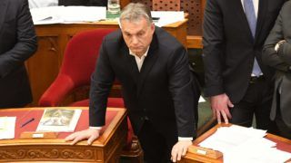 """Hungarian Prime Minister Viktor Orban takes part in a parliament session on December 12, 2018 in Budapest. - Rare scenes of chaos gripped the Hungarian parliament as it passed changes to the labour code proposed by Orban's party that critics have dubbed a """"slave law"""". The bill loosens labour rules by hiking the maximum annual overtime hours that employers can demand from 250 to 400 hours. (Photo by ATTILA KISBENEDEK / AFP)"""