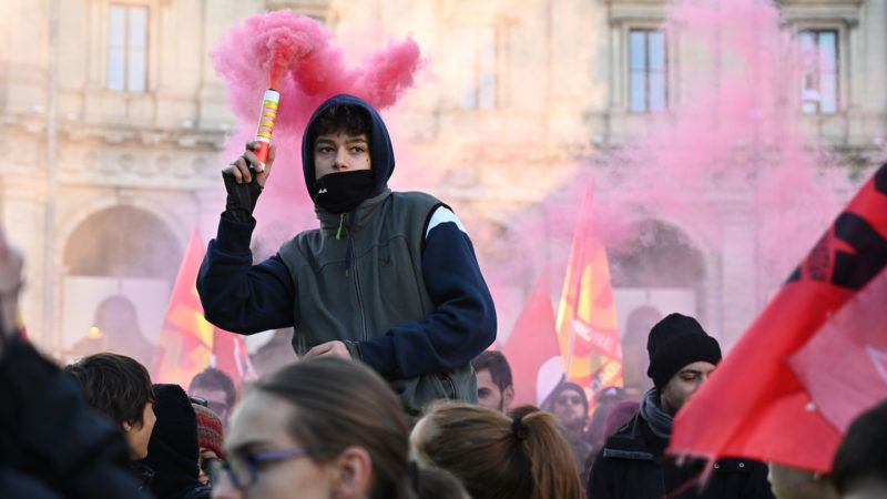 A young man holds a flare as people, members of anti-racism associations and migrants gather on Piazza della Repubblica in central Rome on December 15, 2018 to protest the government's social politics, its recent decree restricting the right to asylum, and against racism. (Photo by Vincenzo PINTO / AFP)