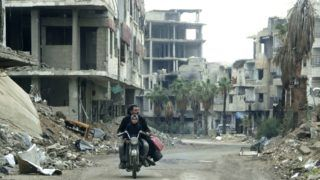 A Syrian man drives past destrpoyed buildings in Arbin on December 18, 2018. - Retaken in the spring by forces loyal to President Bashar al-Assad during a brutal offensive to capture the Eastern Ghouta area, Arbin is everything but festive. Rubble from razed buildings spills out into deserted streets lined with burned-out cars. The town looks more apocalyptic than merry. (Photo by Maher AL MOUNES / AFP)