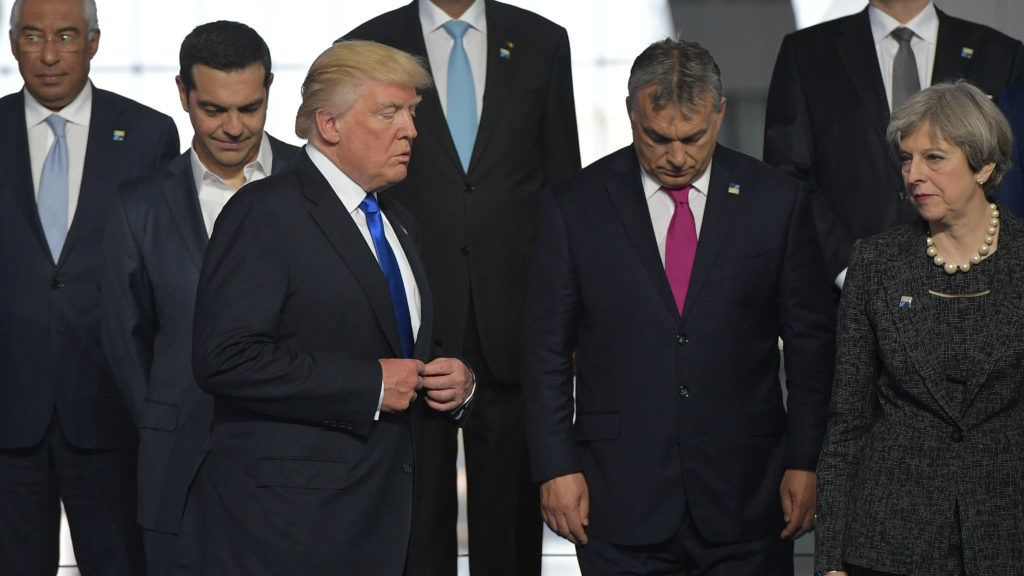 US President Donald Trump (front) arrives for a speech as Britain's Prime Minister Theresa May (R) looks on during the unveiling ceremony of the Berlin Wall monument, during the NATO (North Atlantic Treaty Organization) summit at the NATO headquarters, in Brussels, on May 25, 2017. (Photo by Mandel NGAN / AFP)