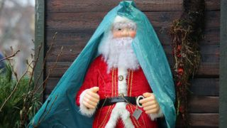 A Santa Claus figure with rain-protective gear stands in Hamburg, Germany, 24 December 2014. Rainy weather dominates Northern Germany on Christmas Eve. PHOTO: MALTE CHRISTIANS/dpa