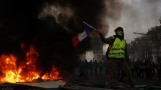 """Yellow vests (Gilets jaunes) protestors shout slogans as material burns during a protest against rising oil prices and living costs near the Arc of Triomphe on the Champs Elysees in Paris, on November 24, 2018.  Police fired tear gas and water cannon on November 24 in central Paris against """"yellow vest"""" protesters demanding French President Emmanuel Macron roll back tax hikes on motor fuel. (Photo by Mehdi Taamallah / Nurphoto) (Photo by Mehdi Taamallah/NurPhoto)"""
