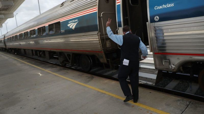 MIAMI, FL - MAY 24: An Amtrak employee prepares to board the train as it pulls out of the Miami station on May 24, 2017 in Miami, Florida. President Donald Trump's budget proposal would terminate federal dollars that supportÊAmtrak's long-distance services, which would potentially mean an elimination of all Amtrak service in Florida.   Joe Raedle/Getty Images/AFP