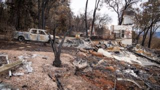 A burned-out vehicle is seen near a destroyed home in Paradise, California, U.S., on Monday, Nov. 26, 2018. The nation's deadliest wildfire in a century known as the Camp Fire that killed at least 85 people and burned over 14,000 homes has been fully contained after burning for more than two weeks, authorities said Sunday. Photographer: David Paul Morris/Bloomberg