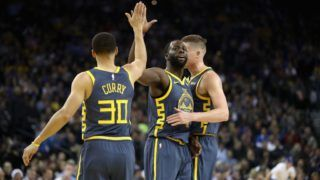 OAKLAND, CA - DECEMBER 12:  Jonas Jerebko #21, Draymond Green #23, and Stephen Curry #30 of the Golden State Warriors congratulate one another after the Warriors made a basket against the Toronto Raptors at ORACLE Arena on December 12, 2018 in Oakland, California.  NOTE TO USER: User expressly acknowledges and agrees that, by downloading and or using this photograph, User is consenting to the terms and conditions of the Getty Images License Agreement.  (Photo by Ezra Shaw/Getty Images)