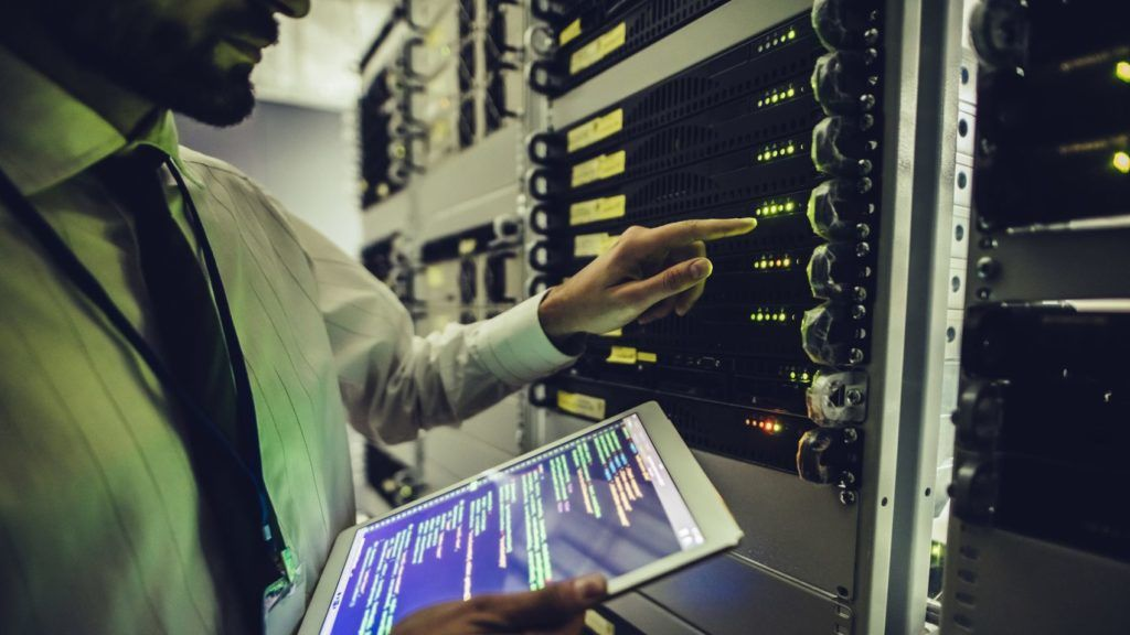 Handsome man is working in data centre with tablet.IT engineer specialist in network server room.Running diagnostics and maintenance.Technician examining server in big data center full of rack servers