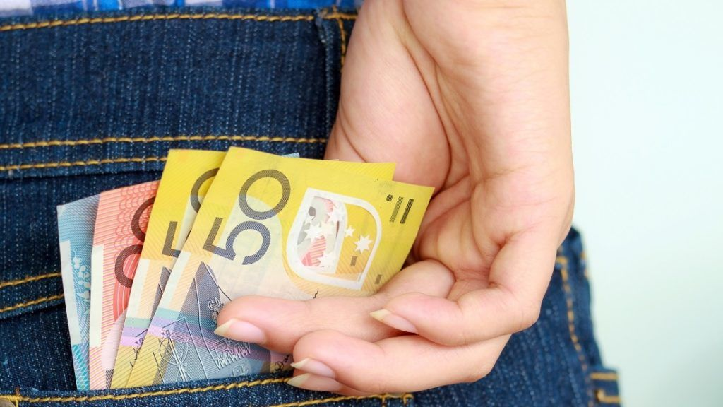 Young girl's hand taking banknote out of jeans pocket