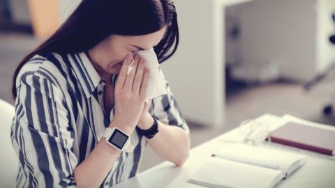 Winter season. Nice beautiful ill woman sitting at the table and sneezing while having a cold