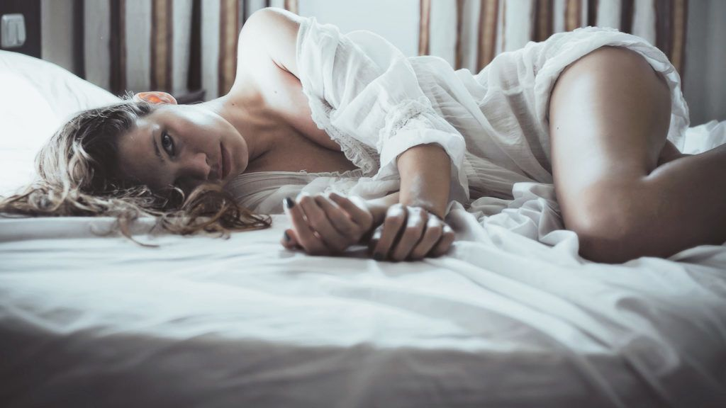 Woman  in bed by window