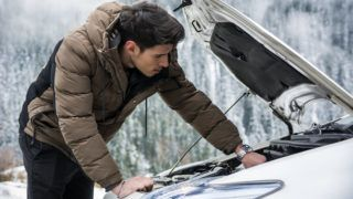 Young man near car with open hood inspecting engine. Snowy forest on background