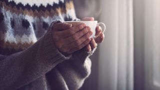 Woman in grey knitted sweater with traditional motifs holding in hands a white cup of hot coffee with steam coming out in the morning light