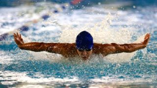 Photo of man athlete during the swim in the pool. Water sport. Sport competition, chempionship, hands from side like wings. Swimmer doing butterfly stroke with face out of water and arms behind back