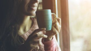 woman standing in front of window and drinking coffee