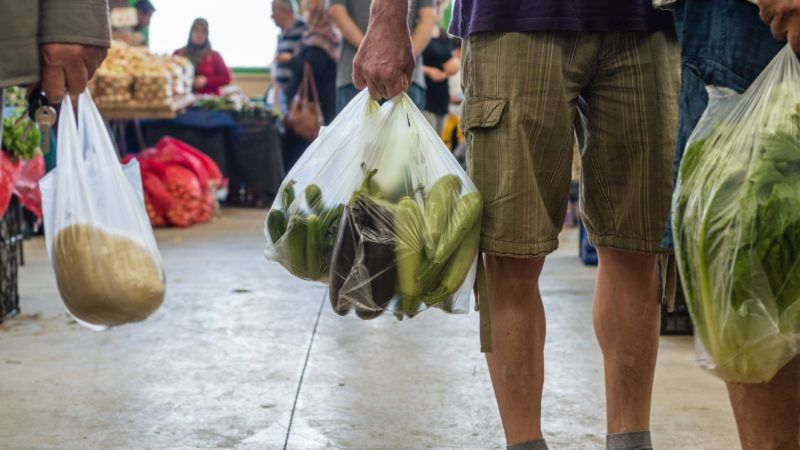 Men holding plastic shopping bag with vegetables in a typical Turkish greengrocery bazaar in Eskisehir, Turkey.