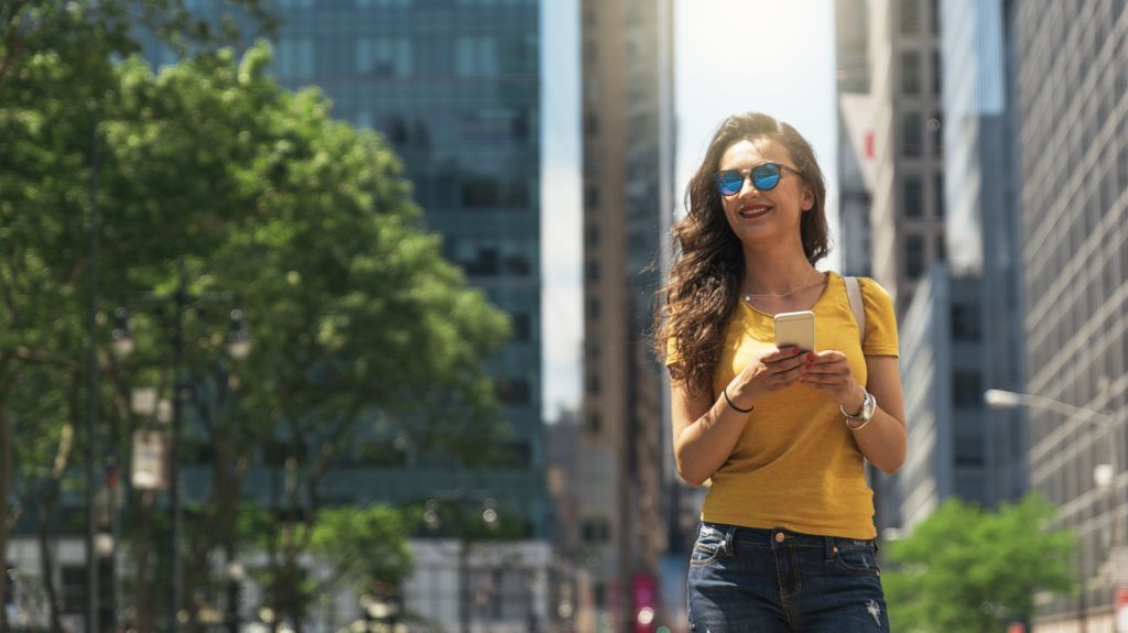 Beautiful woman using phone in the five avenue of New York.