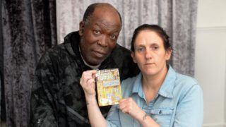 "Eric Walker, 56, with his partner Amanda Emmadi, 36. A National Lottery player insists he has won £200,000 on a scratchcard - despite Camelot saying the ticket has been doctored.  See SWNS story SWLEticket.  Eric Walker, 56, was overjoyed when he scratched the ticket and discovered he had won the jackpot prize on the lotto's Pharaoh's Fortune game.  But his delight turned to heartbreak when Camelot refused to pay out after seeing a picture of the card and claiming it's doctored. Outraged Eric, a father of four from Sheffield, South Yorks, denies tampering with the £3 ticket and says it's ""obvious"" he's won ""fair and square"".  Camelot Group, which is carrying out an investigation, claim it appears a letter F on the card has been changed to an E to turn it into a winning ticket. Eric, who is unemployed and has four children aged between 14 months and nine-years-old, says the money would be ""life changing"".  Eric's card shows that he uncovered three pharaoh symbols on squares D1, E5 and A5, however, the E5 code appears to have been doctored.  The F5 square, which the code was originally believed to have been, is also scratched off. ***EXCLUSIVE***"